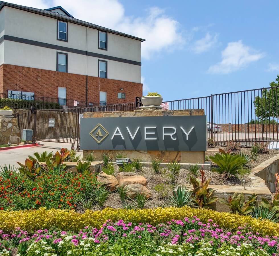 Stone sign for The Avery in front of gated entrance.