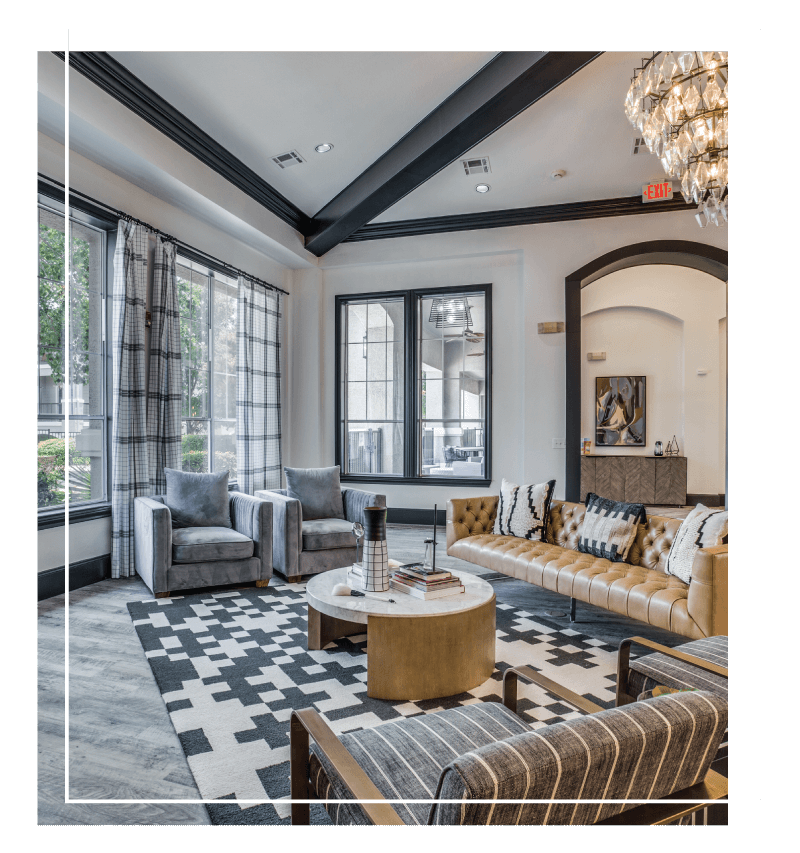 Luxurious lobby with large windows, ample natural light, vaulted ceilings with crown molding, chandelier, and designer furniture.