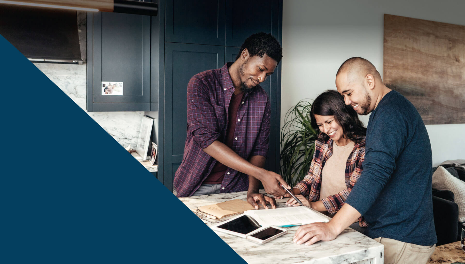 Leasing agent in a luxury kitchen showing documents to a smiling couple.